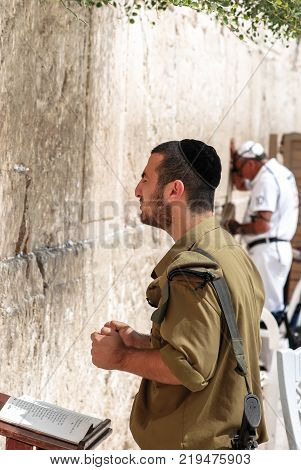 JERUSALEM ISRAEL - AUGUST 03 2010: Vertical picture of Israeli man soldier praying in front of The Western Wall the Kotel at Jewish Quarter inside the walls of Old City in Jerusalem Israel