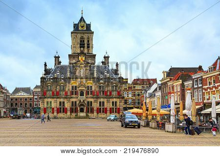 Delft, Netherlands - April 6, 2016: Stadhuis or City Hall, Markt square, houses and people in Delft, Holland