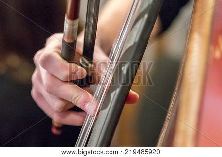 Hand of a girl playing a cello closeup. contrabass