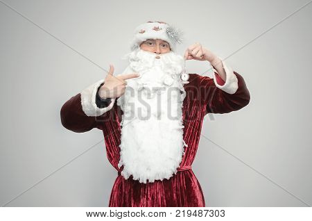 Santa Claus holds in hands a pocket watch with arrow at 12 o'clock time isolated on gray background. In anticipation of Christmas concept.