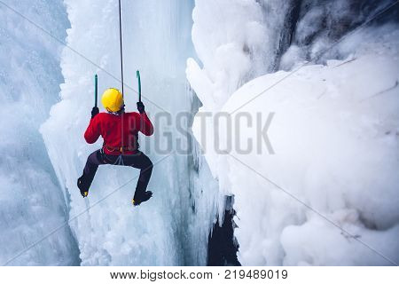 climber climbs the frozen waterfall. ice climbing on ice. The water runs over the skalolaz when it climbs along the route.