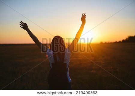 Portrait of happy and enjoying young woman on a meadow on a sunset. Cheerful girl on sunset. Lifestyle and happiness concept. strong confidence woman open arms under the sunrise at seaside