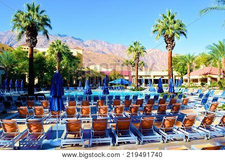 December 18, 2017 in Palm Springs, CA:  Lawn chairs surrounding a pool taken at the Renaissance Hotel in Palm Springs, CA where guests can sunbathe and swim poolside while viewing surrounding gardens and desert mountains beyond