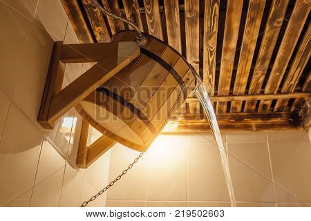 Wooden bucket for Russian bath or sauna. Cold water pours from bucket in the steam room.