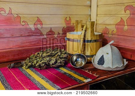 Traditional Russian bath equipment on the wooden bench. Wooden bucket, ladle, oak broom, bath hat and towel.