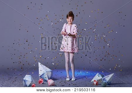 Cute baby girl dresses pretty model enjoying holiday and throwing confetti.happy holidays images.kids party dresses.Cheerful girl in an elegant pink dress with a hair, make-up.