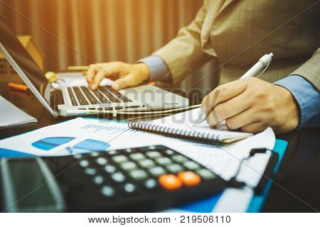 Male bankers are calculating figures on home and property trading taxes infomation.
