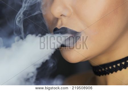 Young, beautiful girl smokes a hookah. It produces smoke from his mouth. The pleasure of smoking. Portrait of girl in a hookah. with the smoke one more view.