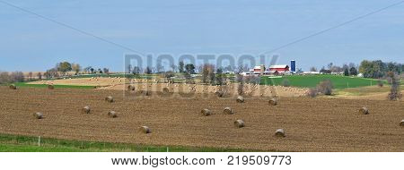 vast Midwest farm land panorama with corn shock bails