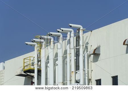 Several white ventilation vents are located next to the building.