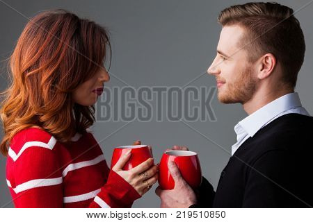 Young couple holding red coffee mags, Valentine's day concept