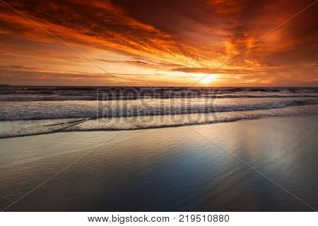 Splashing ocean wave in front of beautiful sunset sky background