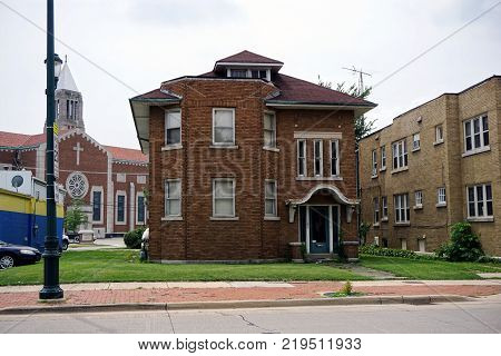 JOLIET, ILLINOIS / UNITED STATES - JULY 26, 2017: A brown brick two-story apartment building, in front the of Cathedral of Saint Raymond Nonnatus, on Plainfield Road in Joliet.