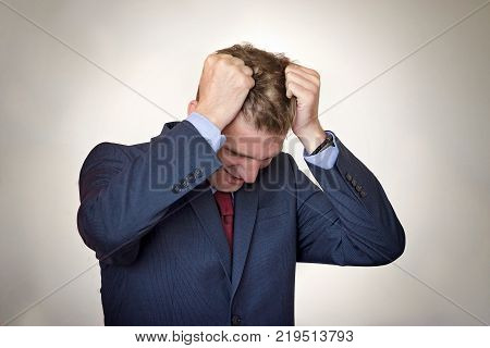 Young man in the suit pulling his hair