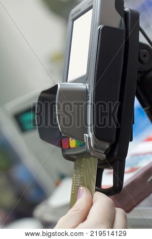 Close up of hand using credit card swiping machine to pay. Hand with credit card swipe through terminal for payment in cafeteria. Man entering credit card code in swipe machine.