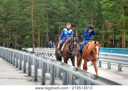 Arshan Russia - August 15 2017: Two Buryat boys ride horses on bridge over the Kyngyrga River. Buryatia