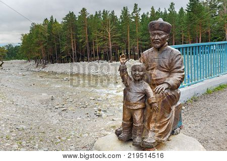 Arshan Russia - August 15 2017: Statue of Man with Child at the bridge over the Kyngyrga River. Buryatia