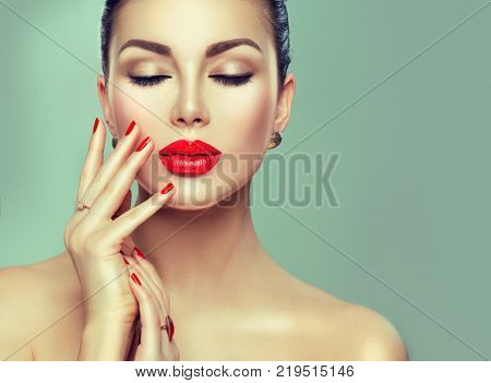 Beautiful Fashion woman model face portrait with red lipstick and red nails. Glamour girl with bright makeup. Beauty female. Perfect skin and make up and manicure. Red lips and nail polish