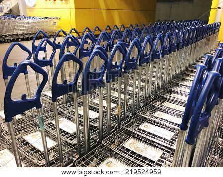 RISHON LE ZION, ISRAEL- DECEMBER 16, 2017: A large group of IKEA shopping carts lined up in rows in trolleys area of IKEA. Founded in Sweden in 1943 Ikea is the world's largest furniture retailer.