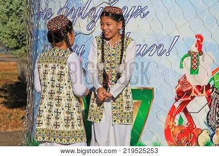ASHGABAT TURKMENISTAN - January 04 2017: Two unknown young girls in national clothes laugh and talk. ASHGABAT TURKMENISTAN - January 04 2017