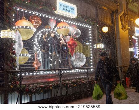 ST. PETERSBURG, RUSSIA - DECEMBER 23, 2017: People at the window of department store DLT decorated for Christmas. Designers of windows was inspired by atmosphere of US in 1920s