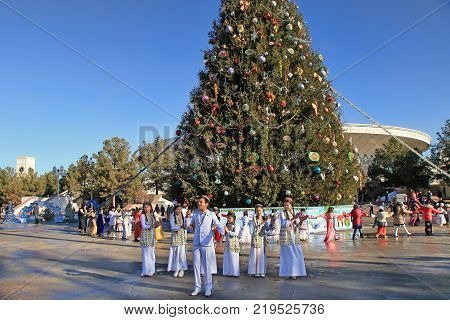 ASHGABAT TURKMENISTAN - January 04 2017: A group of children in national clothes performs on the square near the New Year tree.