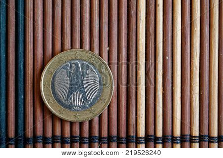 One Euro Coin Lie On Wooden Bamboo Table Denomination Is 1 Euro - Back Side