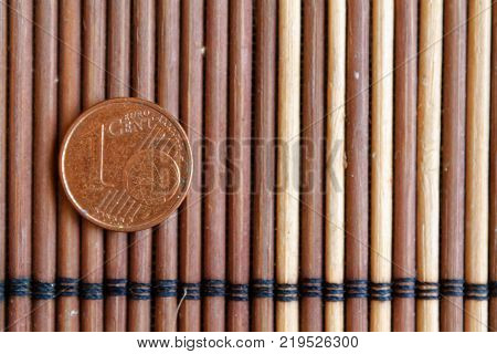One euro coin lie on wooden bamboo table Denomination is one euro cent