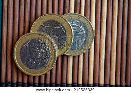 Three Euro Coins Lie On Wooden Bamboo Table Denomination Is 1 Euro