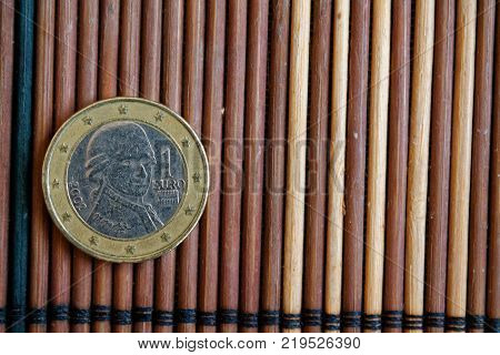 One euro coin lie on wooden bamboo table Denomination is 2 euro - back side