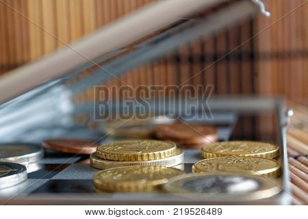 Three Euro Coins Lie On Wooden Bamboo Table In A Row Denomination Is One Euro