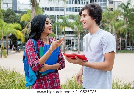 Native latin american female student talking with caucasian friend outdoors on campus of the university