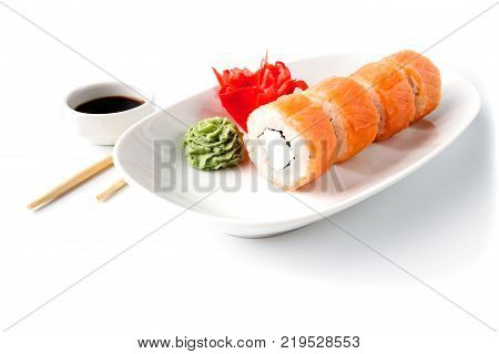 Japanese traditional Cuisine - Roll with Cucumber Cream Cheese with raw Tuna(maguro) inside. on white dish with sticks isolated over white background