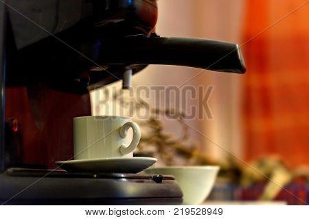 Using coffee maker to prepare coffee. Pouring espresso coffee from coffee machine