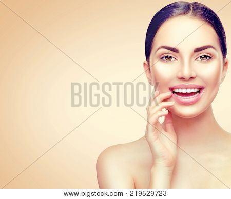 Beauty Portrait. Beautiful Spa Brunette Woman Touching her Face and smiling. Teeth whitening. Perfect Fresh Skin. Pure Beauty Model Girl. Youth and Skin Care Concept. On beige background.
