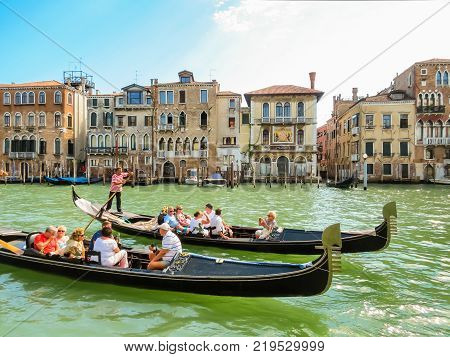 VENICE, ITALY - SEPTEMBER 6, 2013: Traditional Venetian Gondolas on Canal Grande. Popular entertainment for tourists in Venice is gondolas riding. Venice, Italy