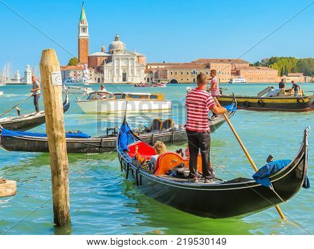 VENICE, ITALY - SEPTEMBER 6, 2013: Gondolier floating in the Venetian lagoon. Popular entertainment for tourists in Venice is gondolas riding. Venice, Italy