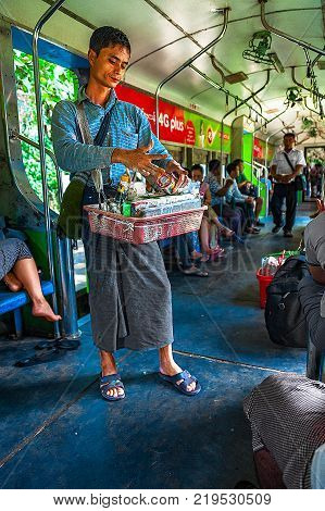 Yangon, Myanmar - Oct 22, 2017: A seller on the Yangon Circular Line is preparing areca nut with slaked lime paste and wrapped it in betel leaf to a customer. The betel chewing is a Myanmar culture.