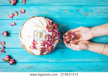 Woman's hands hold the dry rose. The white cream cake decorated dry rose on blue wood background. Top view