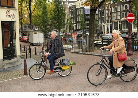 AMSTERDAM/ NETHERLANDS - OCTOBER 25, 2014. An elegantly dressed elderly couple riding the bicycles in the historical center. The intersection of the Prinsengracht and Leidsegracht canal, Amsterdam, the Netherlands.