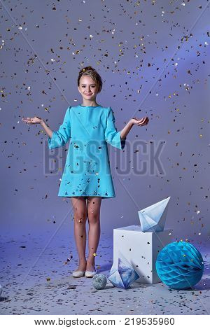 Cute baby girl dresses pretty model enjoying holiday and throwing confetti.happy holidays images.kids party dresses.Cheerful girl in an elegant turquoise dress with a hair, make-up.Minimalism and origami