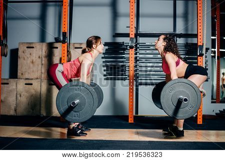 Sportive athletic womans lifting heavy barbells in light spacious gym. two girls face each other lift barbells