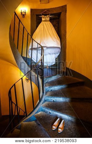 Wedding dress hanging on a spiral staircase and wedding shoes.