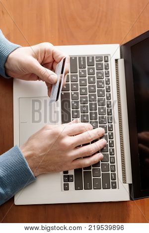 Online gambling. Man holding credit card and betting at virtual casino on his laptop. Luck success and winning concept