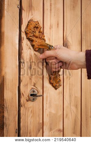 Female Hand Open Wooden Door Of Bath Behind Obsolete Painted Iron Handle Close Up.
