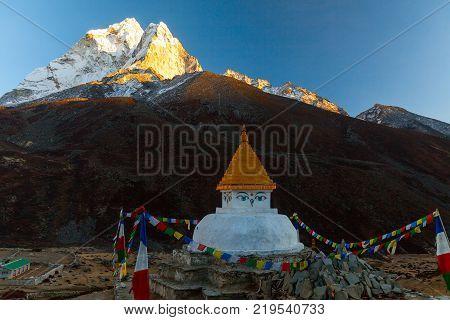 Buddhist stupa on mountain trekking path in Himalayas, Nepal.