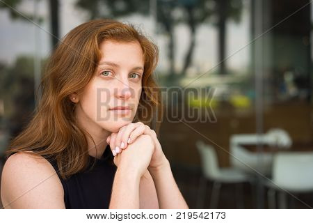 Closeup of serious young woman sitting at office cafe resting chin on hands. Young female manager thinking over great challenge. Business and challenge concept