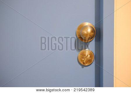Door knob and keyhole on blue wooden door