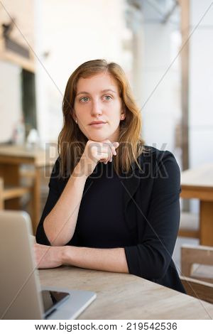 Portrait of pensive woman at cafe with laptop waiting for waiter. Female office worker on her break for lunch. Business lunch and work balance concept
