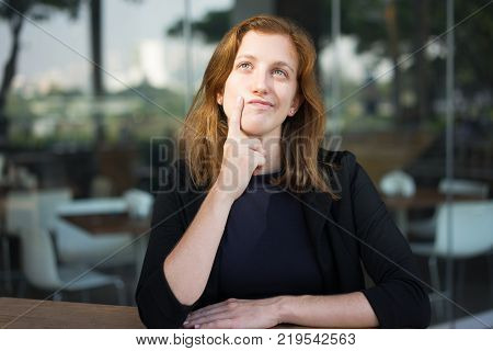Portrait of attractive young woman sitting at outdoor office cafe and looking upward with finger on chin. Businesswoman thinking over lucrative offer during her break. Work balance concept